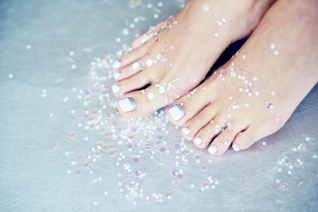 Weibliche füße mit farbiger pediküre Premium Fotos