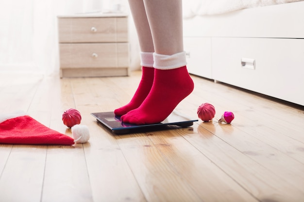 Weibliche füße stehen auf elektronischen waagen zur gewichtskontrolle in roten socken mit weihnachtsdekoration Premium Fotos