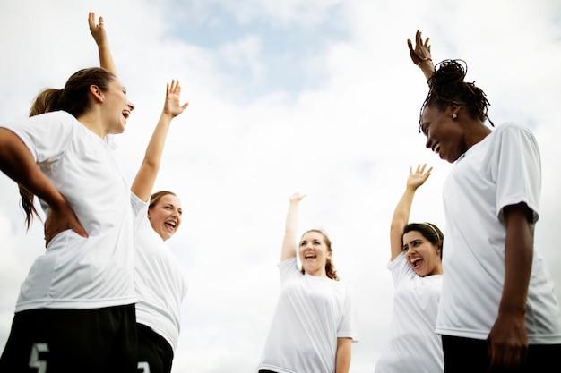 Weibliche fußballspieler, die auf dem feld zujubeln Premium Fotos