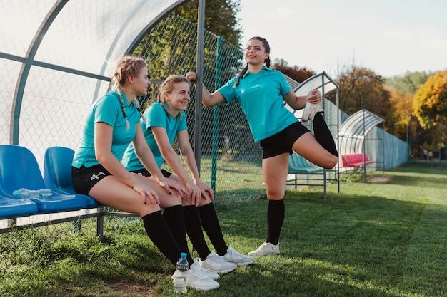 Weibliche fußballspieler, die auf einer bank sitzen Kostenlose Fotos