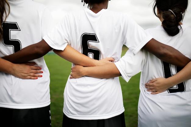 Weibliche fußballspieler, die zusammen kuscheln und stehen Premium Fotos