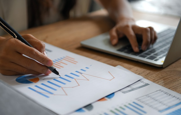 Weibliche geschäftsleute zeigen mit dem stift auf das datendiagramm und arbeiten mit dem laptop. Premium Fotos