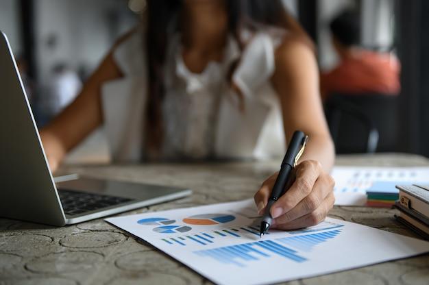 Weibliche geschäftsmänner überprüfen datendiagramme und verwenden laptop. sie zeigte mit dem stift auf die grafik vorne. Premium Fotos