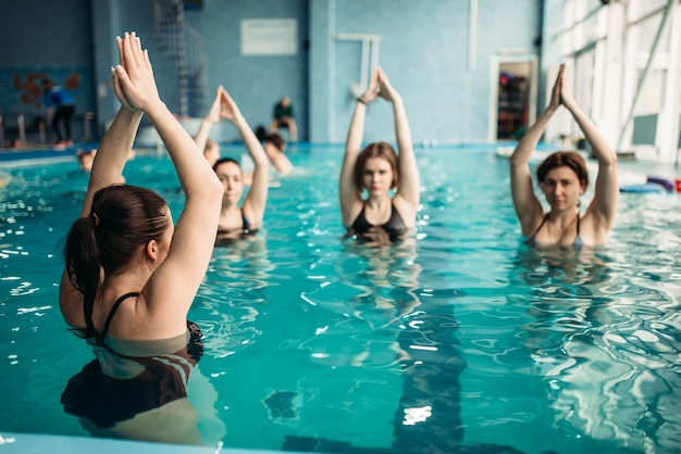 Weibliche gruppe auf aqua-aerobic-training im schwimmbad. frauen in badebekleidung auf training, wassersport Premium Fotos