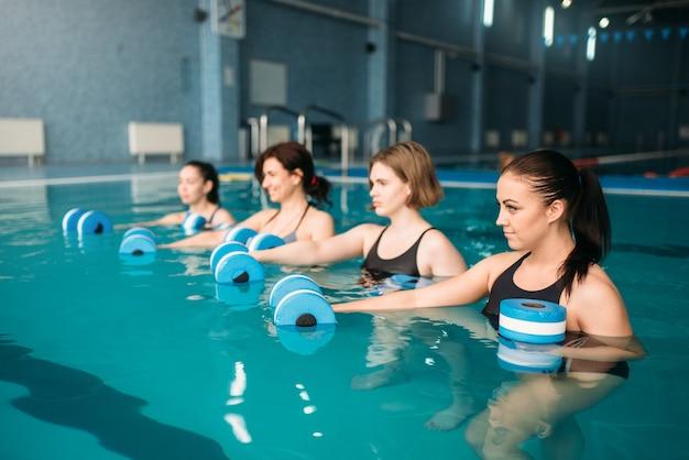 Weibliche gruppe, die übung mit hanteln auf aqua-aerobic-training im schwimmbad tut. frauen in badebekleidung auf training, wassersport Premium Fotos