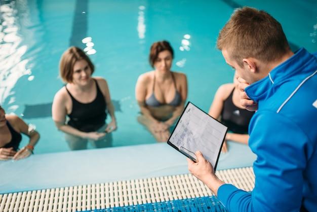 Weibliche gruppe mit männlichem trainer, aqua-aerobic im schwimmbad. frauen in badebekleidung auf training, wassersport Premium Fotos