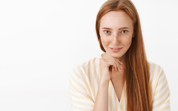 Weibliche gut aussehende flirty rothaarige frau mit sommersprossen im niedlichen v-ausschnitt kleid, das hand auf kiefer hält und mit sinnlichem verführerischem blick lächelt Kostenlose Fotos
