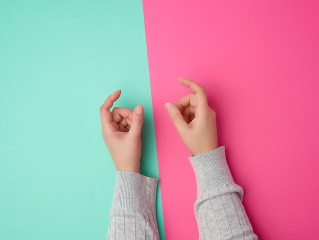Weibliche hände auf einem grünen rosa, finger in der geste des haltens des themas Premium Fotos