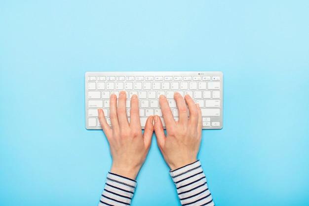 Weibliche hände auf einer tastatur auf einer blauen oberfläche. konzept der büroarbeit, freiberuflich, online. . flachgelegt, draufsicht Premium Fotos
