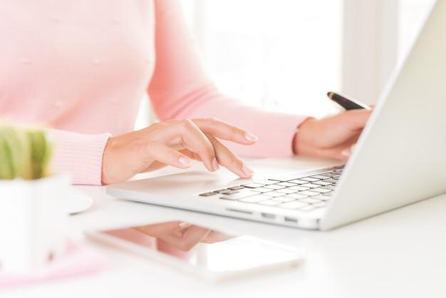 Weibliche hände der nahaufnahme, die auf laptoptastatur schreiben. frau, die zu hause büro bearbeitet Premium Fotos