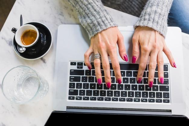 Weibliche hände, die auf laptop schreiben Kostenlose Fotos