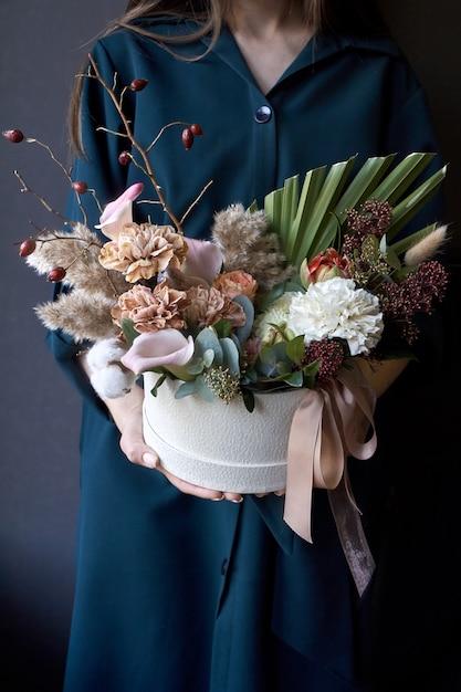 Weibliche hände, die einen kasten mit einem weinleseblumenstrauß auf einem dunklen hintergrund halten Premium Fotos