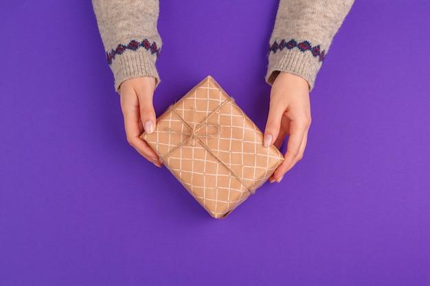 Weibliche hände, die eingewickeltes geschenk auf purpurrotem hintergrund halten Premium Fotos