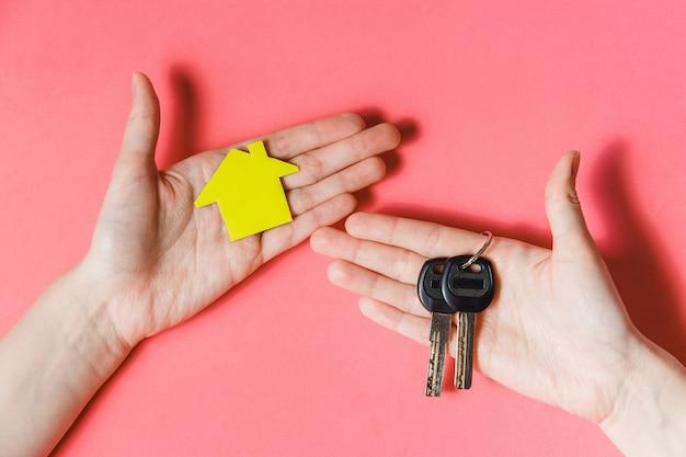 Weibliche hände, die gelbes papierhaus und schlüssel halten Premium Fotos