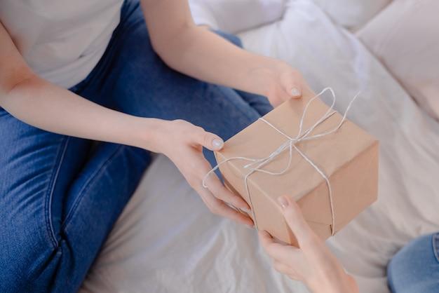 Weibliche hände, die geschenk halten. geschenk mit bastelpapier umwickelt. Premium Fotos