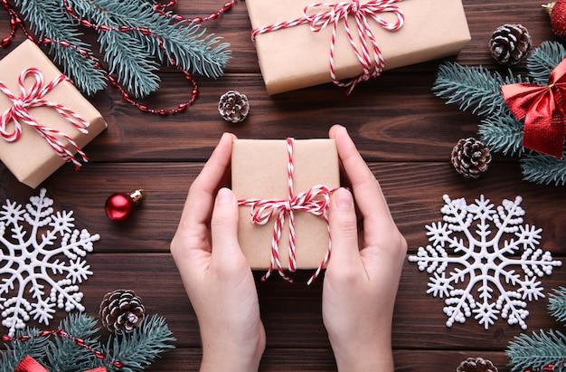Weibliche hände, die geschenkbox auf braunem holztisch halten Premium Fotos