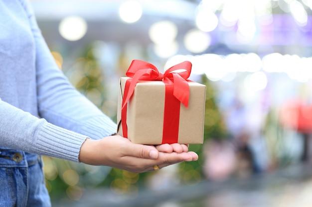 Weibliche hände, die geschenkbox mit rotem band für weihnachten und neujahr oder grußjahreszeit, valentinstag halten Premium Fotos