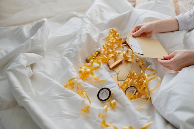 Weibliche hände, die geschenkkarte, umschlag und geschenkbox über der bettdecke halten. neujahr und weihnachten konzept. horizontale ansicht von oben Premium Fotos