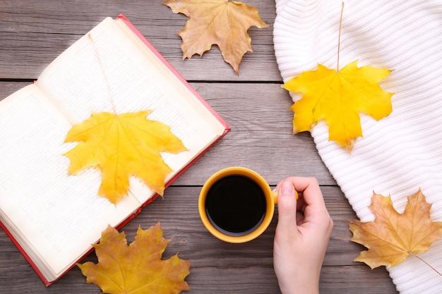 Weibliche hände, die schale schwarzen kaffee mit herbstlaub und buch auf grau halten Premium Fotos