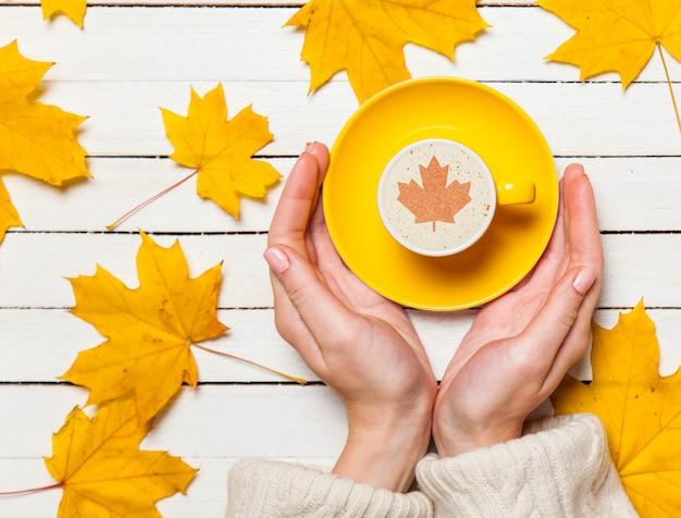 Weibliche hände, die tasse kaffee auf holztisch halten. Premium Fotos