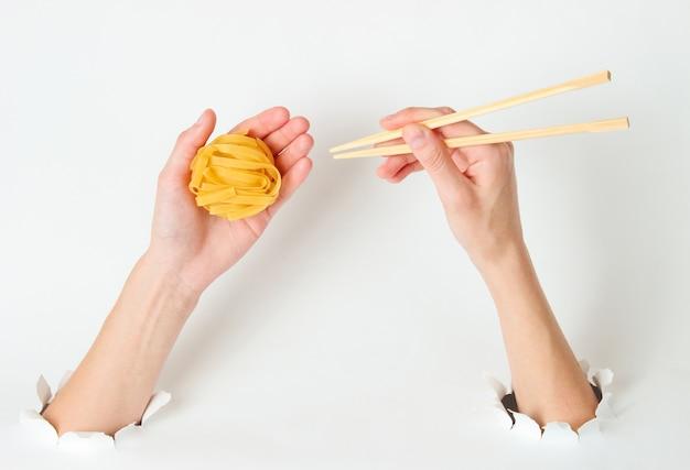 Weibliche hände halten rohe tagliatelle-nudeln und essstäbchen auf weiß mit zerrissenem loch. minimalistisches lebensmittelkonzept. draufsicht Premium Fotos