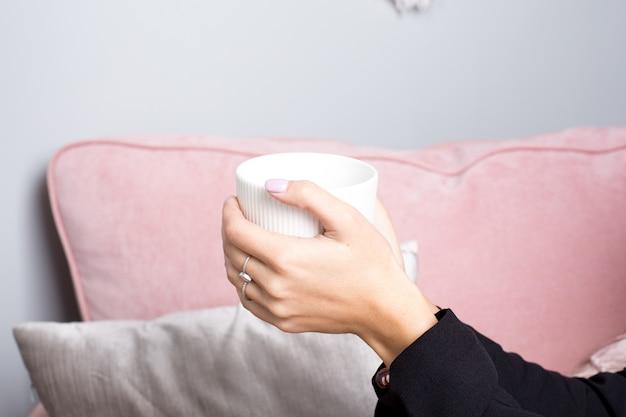 Weibliche hände halten tee im weißen keramischen becher in einem rosa innenraum Premium Fotos