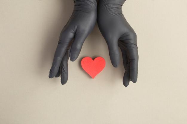 Weibliche hände in den schwarzen handschuhen und im roten herzen auf dem grauen hintergrund Premium Fotos