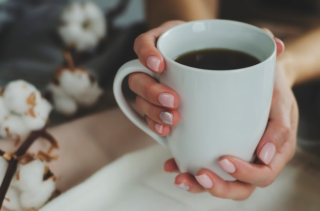 Weibliche hände mit der pastell farbigen maniküre, die einen weißen becher mit getränk auf hellem hintergrund hält Premium Fotos