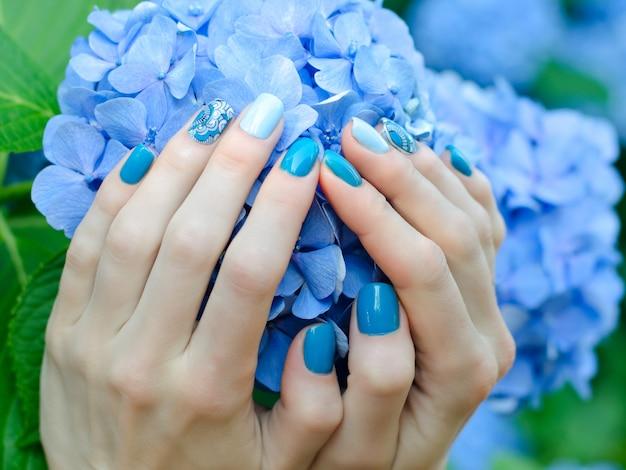 Weibliche hände mit einer schönen maniküre auf einer blauen blume Premium Fotos