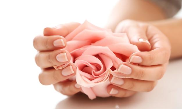 Weibliche hände mit rosa rose. weiblichkeitskonzept Kostenlose Fotos