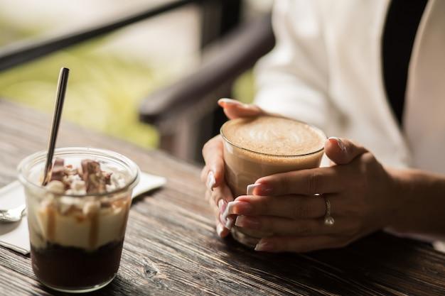 Weibliche hände mit schöner manikürenahaufnahme halten eine schale mit heißem kaffee auf einem holztisch Premium Fotos