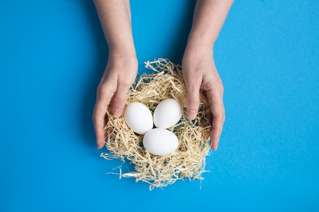 Weibliche hände mit weißen hühnereiern in einem strohnest auf der blauen oberfläche Premium Fotos