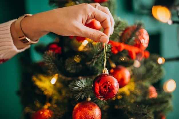 Weibliche hände schließen oben und verzieren weihnachtsbaum mit roten bällen Kostenlose Fotos