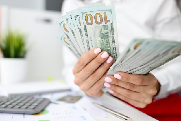 Weibliche hände zählen hundert dollarnoten neben dem taschenrechner. Premium Fotos