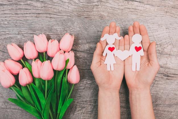 Weibliche hände zeigen zwei papierleute, einen mann und eine frau, auf einem hölzernen hintergrund. valentinstag Premium Fotos