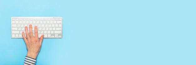Weibliche hand auf einer tastatur auf einer blauen oberfläche. konzept der büroarbeit, freiberuflich, online. . flachgelegt, draufsicht Premium Fotos