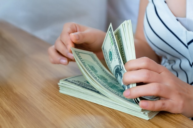 Weibliche hand des selektiven fokus, die banknote zählt Premium Fotos