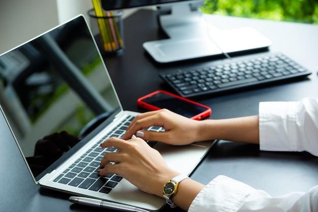 Weibliche hand, die auf tastatur des laptops schreibt Kostenlose Fotos