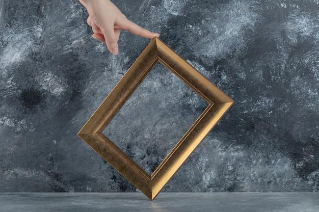 Weibliche hand, die bilderrahmen auf marmor berührt. Kostenlose Fotos
