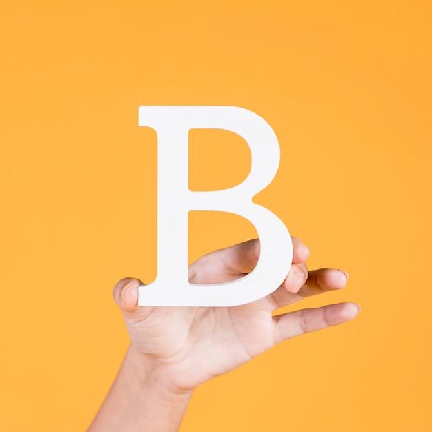 Weibliche hand, die den weißen versalienbuchstaben b zeigt Kostenlose Fotos
