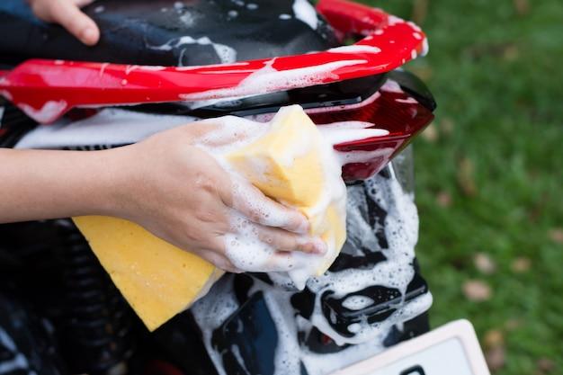 Weibliche hand, die ein motorrad wäscht. Premium Fotos