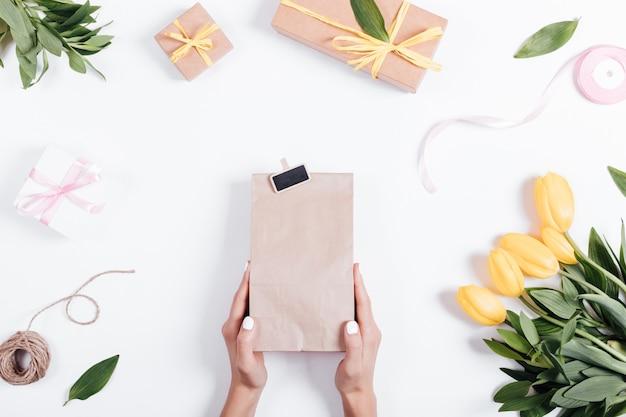 Weibliche hand, die eine papiertüte mit einem geschenk auf einer tabelle nahe den tulpen, den bändern und den kästen hält Premium Fotos
