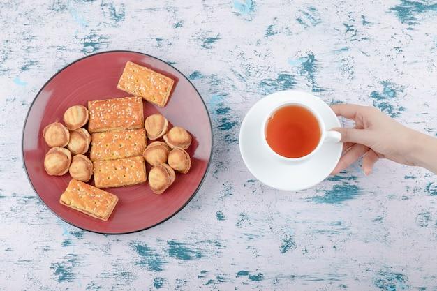 Weibliche hand, die eine tasse tee mit shortbread-nüssen mit kondensmilch hält. Kostenlose Fotos