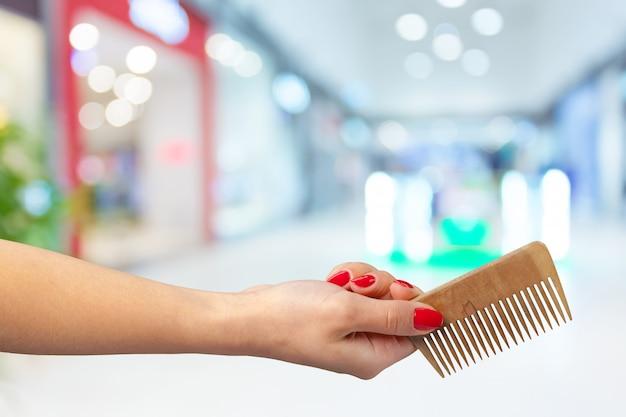 Weibliche hand, die friseurkamm im kosmetischen speicher hält Premium Fotos