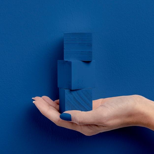 Weibliche hand, die gestapelte würfel hält Kostenlose Fotos