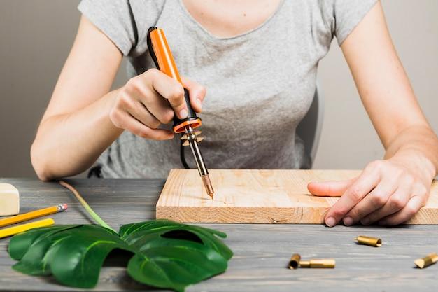 Weibliche hand, die harte hölzerne form unter verwendung der lötmaschine nahe monstera blatt auf tabelle schneidet Kostenlose Fotos