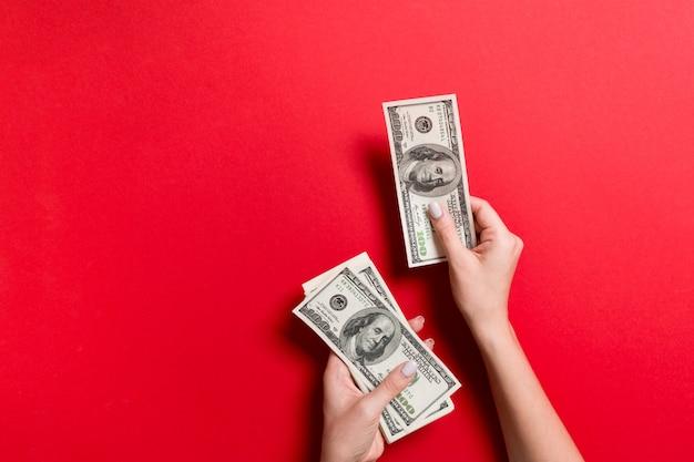 Weibliche hand, die hundert dollarbanknoten gibt Premium Fotos