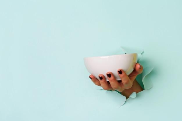 Weibliche hand, die leere schüssel auf blauem hintergrund mit kopienraum hält. Premium Fotos