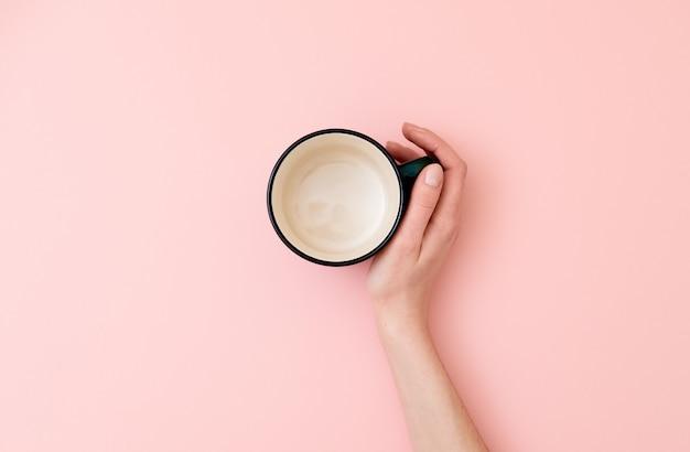 Weibliche hand, die leeren becher auf rosa hintergrund hält. Premium Fotos