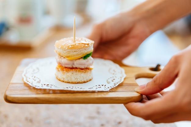 Weibliche hand, die mini chicken burger auf hölzernem hackendem brett mit unschärfehintergrund dient. Premium Fotos